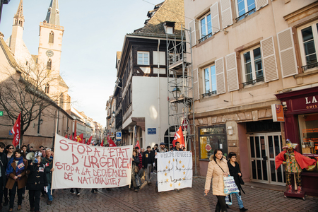 precarious: STRASBOURG, FRANCE - FEB 6, 2016: Protesters marching during a demonstration in the city center against governments plan to extent the state of emergency and for opened borders Editorial