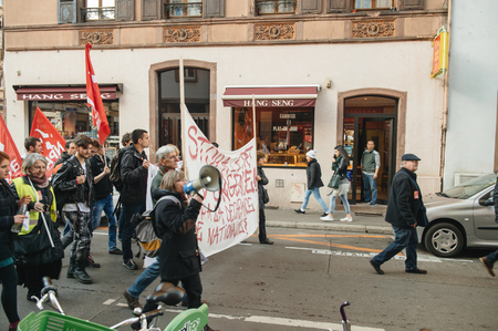 precarious: STRASBOURG, FRANCE - FEB 6, 2016: Chinese restaurant employee looking at protesters marching during a demonstration against governments plan to extent the state of emergency and for opened borders -