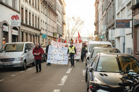 extent: STRASBOURG, FRANCE - FEB 6, 2016: Protesters marching during a demonstration in the calm street against governments plan to extent the state of emergency and for opened borders