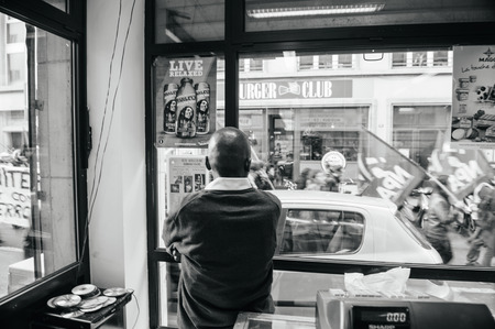 extent: STRASBOURG, FRANCE - FEB 6, 2016: Black ethnicity shop owner looking from the store to the protesters marching during a demonstration against governments plan to extent the state of emergency and for opened borders