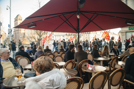 extent: STRASBOURG, FRANCE - FEB 6, 2016: Restaurant visitors looking at protesters marching during a demonstration against governments plan to extent the state of emergency and for opened borders
