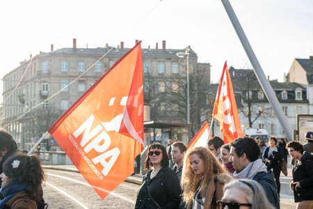 extent: STRASBOURG, FRANCE - FEB 6, 2016: Communist flags in hands of protesters marching during a demonstration against governments plan to extent the state of emergency and for opened borders