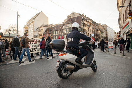 precarious: STRASBOURG, FRANCE - FEB 6, 2016: Police surveilling protesters marching during a demonstration against governments plan to extent the state of emergency and for opened borders