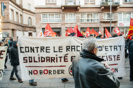 precarious: STRASBOURG, FRANCE - FEB 6, 2016: Protesters marching during a demonstration on tramway rails against governments plan to extent the state of emergency and for opened borders Editorial
