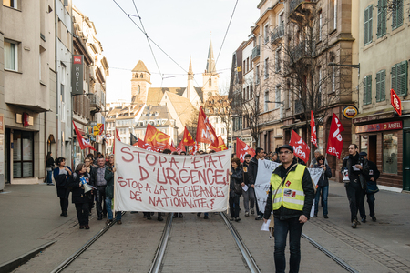 extent: STRASBOURG, FRANCE - FEB 6, 2016: Protesters marching on tram lines during a demonstration against governments plan to extent the state of emergency and for opened borders