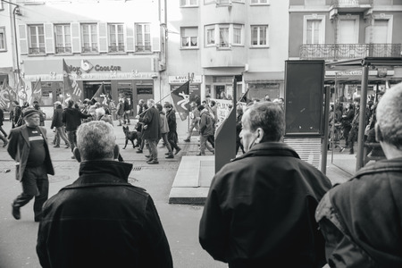 turkish ethnicity: STRASBOURG, FRANCE - FEB 6, 2016: Turkish ethnicity men looking at protesters marching during a demonstration against governments plan to extent the state of emergency and for opened borders -