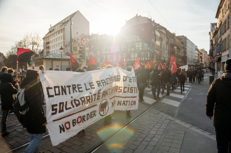extent: STRASBOURG, FRANCE - FEB 6, 2016: Protesters marching in the center of Alsacian city during a demonstration against governments plan to extent the state of emergency and for opened borders Editorial