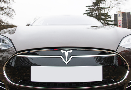 electric vehicle: PARIS, FRANCE - NOV 29, 2014: Luxury Tesla frontal view of badge head-lights and logo are seen below the hood of the Model S electric vehicle on European city street