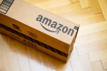 PARIJS, FRANKRIJK - 28 januari 2016: Amazon logo gedrukt op kartonnen doos kant van bovenaf gezien op een houten parwuet vloer. Amazon is een Amerikaanse elektronische e-commerce bedrijf distributie worlwide e-commerce producten
