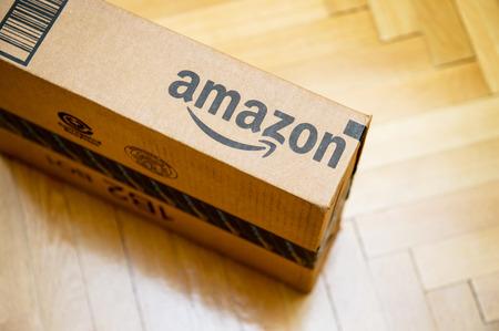 PARIS, Francja - 28 stycznia 2016: Amazon logo drukowane na boku karton widziany z góry na drewnianej podłodze parwuet. Amazon jest amerykańskim elektronicznego e-commerce spółki dystrybucyjnej worlwide towarów e-commerce