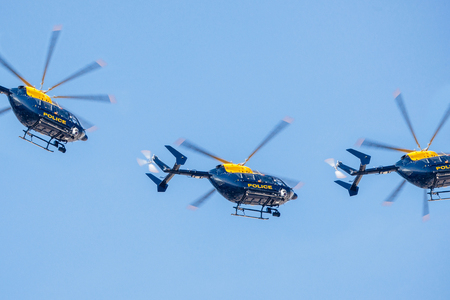 LONDON, UNITED KINGDOM - AUGUST 28, 2013: Three police helicopter flying against a clear blue sky on a summer day Editorial