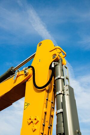 making earth: Hydraulic excavator arm - industrial equipment as seen on construction site agains beautiful blue sky