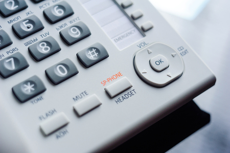 dialplate: Detail of executive VoIP desk phone buttons. Shallow depth of field - focus on the center of the phone