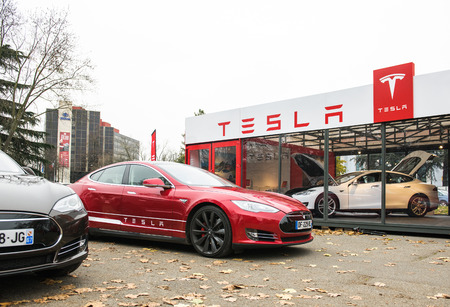 car show: PARIS, FRANCE - NOVEMBER 29: Tesla Model S showroom and two luxury tesla cars outside and one inside. Tesla is an American company that designs, manufactures, and sells electric cars Editorial