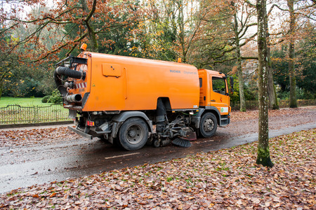 BADEN, BADEN, GERMANY - NOV 20, 2014: Orange Bucher CityFant 60 street sweeper machine cleaning the street after in fall from fallen foliage Editorial