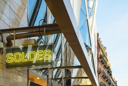 store sign: Neon sign with word SOLDES transalted as SALES from french on the corner of retail store building facade Editorial
