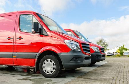 Rij van twee rode generieke bestelwagens voor levering en service naast fabrieks- en magazijndistributiefabriek