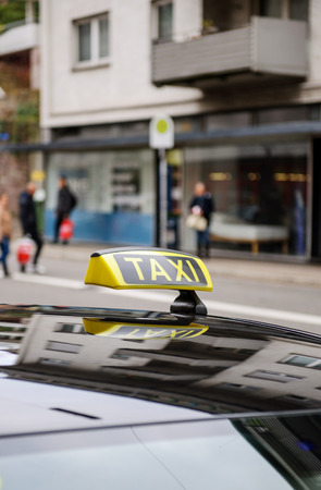 taxi sign: Taxi sign waiting for customers in city with defocused pedestrians and buildings