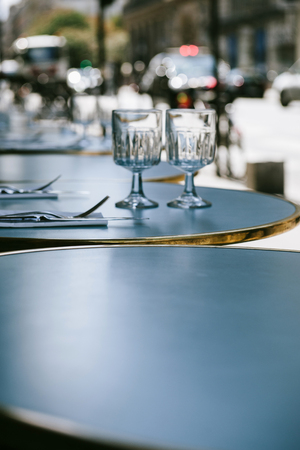 romatic: Parisian street restaurant cafe with defocused background - round table is set in the most romatic city - Paris, France
