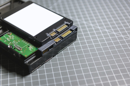 solid state drive: Ssd disk solid state drive above the HDD hard disk drive disk on hacker table Stock Photo