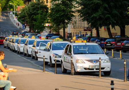 BRASOV, ROMANIA - JUL 5, 2015: Taxi drivers waiting for customers next to rows of Renault Dacia Logan taxis in the city of Brasov, Romania Editorial