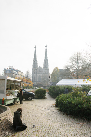 unneeded: BADEN-BADEN, GERMANY - NOV 20, 2014: Beggar on the street of the Baden-Baden in Germany, on a market day in the central Market with impressive view to the Baden Cathedral Editorial