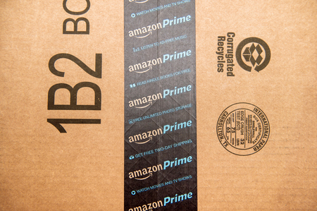 PARIS, FRANCE - JAN 28, 2016: Amazon Prime logotype printed on cardboard box security scotch tape. Amazon Prime is a service from Amazon which delivers parcels in 1 day, streams unlimited music and video gives access to unlimited Books on Kindle store. 報道画像