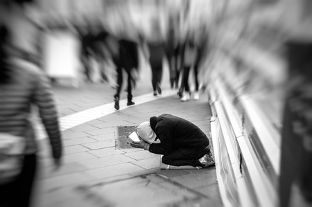 unneeded: People passing indifferently next to beggar in the street of the modern city