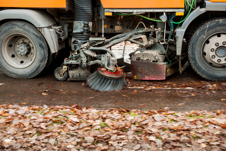 sweeper: Orange street sweeper machine cleaning the street after in fall from fallen foliage