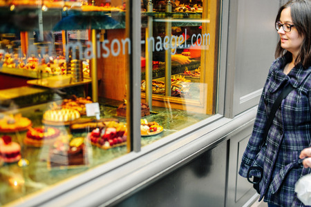 boulangerie: STRASBOURG, FRANCE - MARCH 21, 2015: Woman admiring French sweet pastry food in typical French boulangerie saloon - tilt-shift defocused view