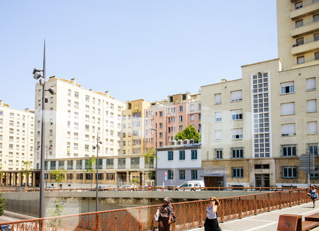 f 18: MARSEILLE, FRANCE - JUL 18, 2014: Center of the city f Marseilles with people walking on bridge on a sunny day with large apartment buildings behind. Marseilles is the largest conglomerate of south of France Editorial