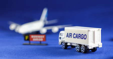 background blue: Air Cargo truck heading defocusing silhouette of an airplane - toy models