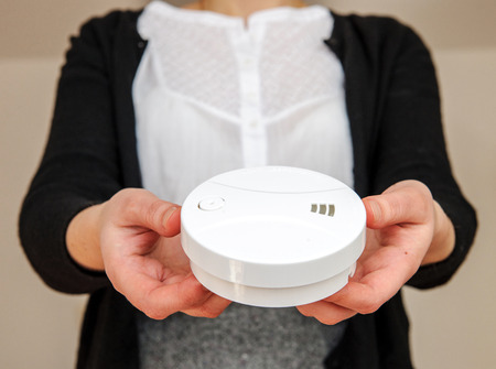 of the senses: Woman holding white smoke detector - the device that senses smoke, typically as an indicator of fire