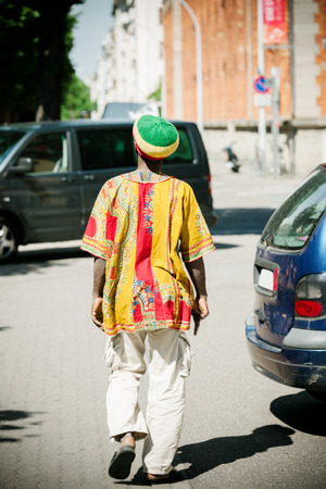 rasta hat: Rastaman wearing tradition al rasta hat, white pants and colorful traditional motive shirt walking on the streets of a modern city