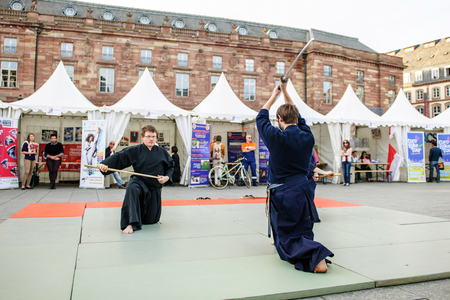 public demonstration: STRASBOURG, FRANCE - APRIL 24, 2015: Samurai sword public demonstration by two men wearing traditioanl samurai Hakama in Place Kleber, Strasbourg, Alsace, Eurometropole Editorial