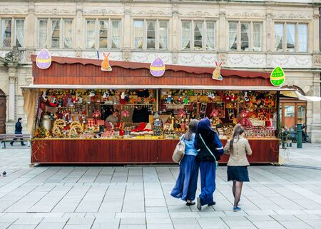 gutenberg: STRASBOURG, FRANCE - MARCH 21, 2015: Three friends visiting Traditional Easter market stall chalet on Old Town Square of Gutenberg