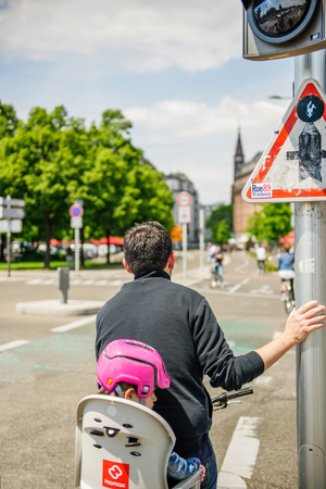 helmet seat: STRASBOURG, FRANCE - MAy 23, 2015: Rear view of man on a bicycle with little girl behind waiting for green light to cross the intersection