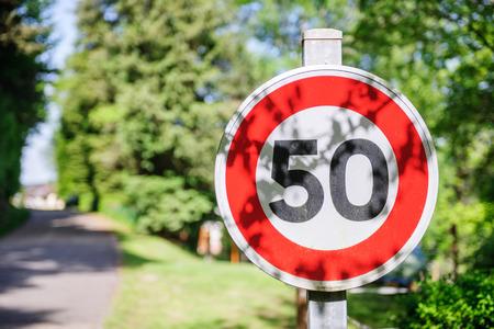 signe ou signe de route Avertissement pour la limite de vitesse maximale sur une journée d'été ensoleillée dans la ville verte. fichier utile pour votre brochure de sécurité