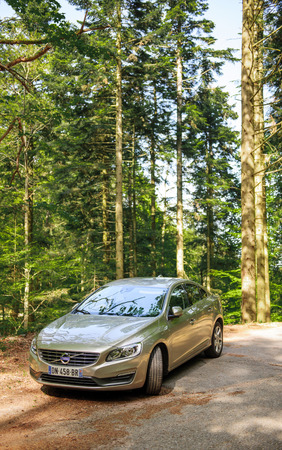 electric automobile: FRANCE - MAY 10, 2015: Electric Hybrid Volvo S60 executive car parked in the middle of green forest. Volvo Hybrid Electric Vehicle is considered one of the most safe and environmentally protective automobile