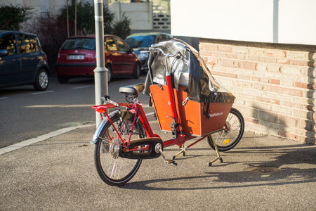 ensures: STRASBOURG, FRANCE - DEC 25, 2015: Cargo bike with protect tent parked on the street. The cargobike made by Bakfiets netherlands is a transport bicycle thats user friendly and ensures absolute cycling pleasure