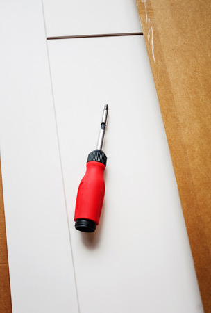 purchased: Screwdriver on a board in the process of setting up recently purchased furniture.  Tilt shift-lens intentionally used for a better focus on the object. Stock Photo