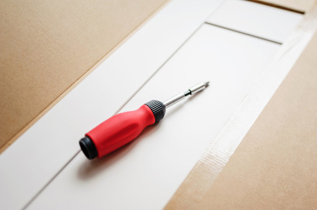 purchased: Red  screwdriver on a board in the process of setting up recently purchased furniture.  Tilt shift-lens intentionally used for a better focus on the object. Stock Photo