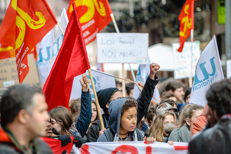 nationwide: STRASBOURG, FRANCE - 9 MAR 2016: Protester with rised hands in front row of thousands of people demonstrating as part of nationwide day of protest against proposed labor reforms by Socialist Government