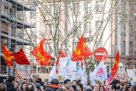 proposed: STRASBOURG, FRANCE - 9 MAR 2016: Communist flags waving as thousands of people demonstrate as part of nationwide day of protest against proposed labor reforms by Socialist Government Editorial