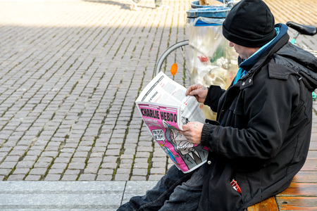 satirical: STRASBOURG, FRANCE - 9 MAR 2016:  Man reading satirical magazine Charlie Hebdo in Place Kleber, Strasbourg France, Alsace