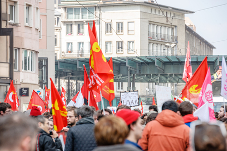 reforms: STRASBOURG, FRANCE - 9 MAR 2016: Communist flags waving as thousands of people demonstrate as part of nationwide day of protest against proposed labor reforms by Socialist Government Editorial