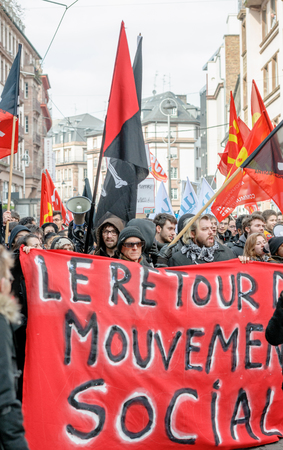socialist: STRASBOURG, FRANCE - 9 MAR 2016: Red socialist banner in front of crowd as thousands of people demonstrate as part of nationwide day of protest against proposed labor reforms by Socialist Government