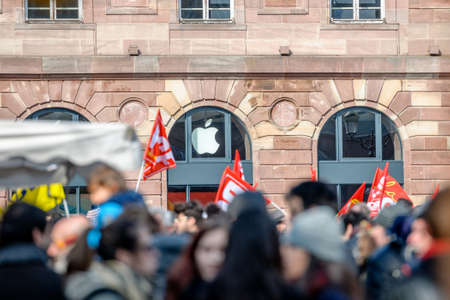reforms: STRASBOURG, FRANCE - 9 MAR 2016: Apple store logo and Communist Flags as thousands of people demonstrate as part of nationwide day of protest against proposed labor reforms by Socialist Government Editorial
