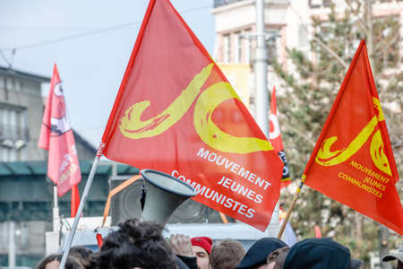 proposed: STRASBOURG, FRANCE - 9 MAR 2016:Megaphone and communist flag as thousands of people demonstrate as part of nationwide day of protest against proposed labor reforms by Socialist Government