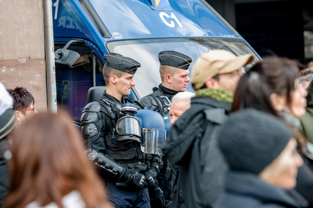 proposed: STRASBOURG, FRANCE - 9 MAR 2016: Police officers surveilling street as thousands of people demonstrate as part of nationwide day of protest against proposed labor reforms by Socialist Government